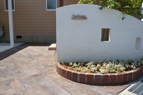 曲線の塗り壁門柱とスタンプコンクリート木目の通路